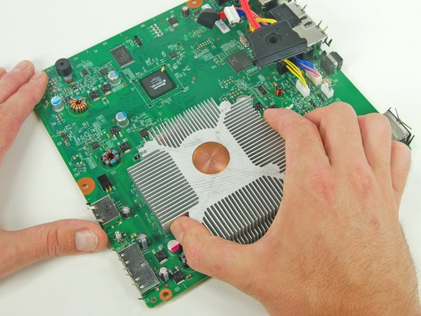 Using one hand to hold the heat sink in place, carefully turn the logic board over.