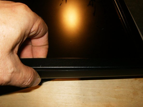 This close-up shows the position of the fingertip to remove the bezel.