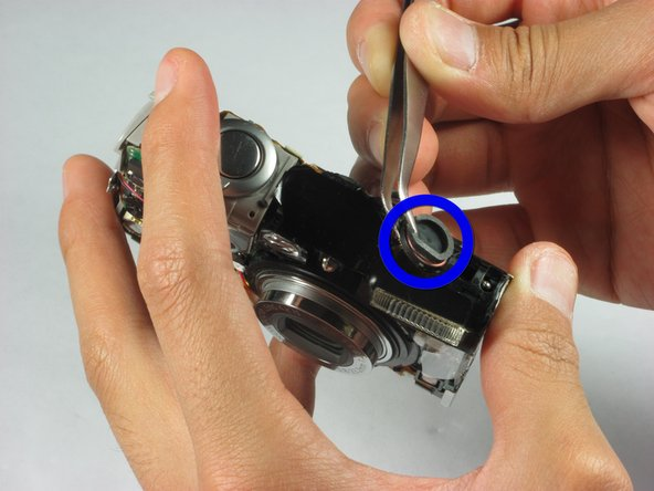 Use a set of tweezers to remove the speaker located at the top of the camera on the flash unit.