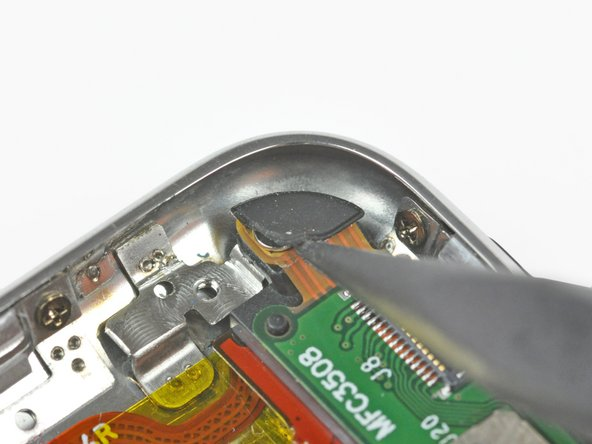 Use the tip of a spudger to peel back the protective rubber grommet to reveal a hidden Phillips screw.