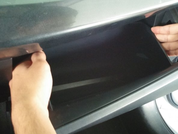 Using both hands, apply inward pressure to the sides of the glove compartment until the compartment is free to slide out.