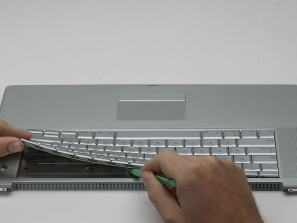 Lay the casing flat so that the keyboard faces up and and slowly pry the keyboard up, beginning at the back edge along the 'F' keys, and moving toward the space bar.