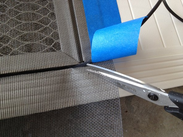 Once you reach the bottom (taped) edge, partially remove the tape to make another diagonal cut in the mesh.