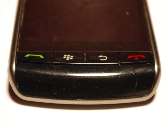 Turn the phone over and remove the plastic cover under the buttons as shown.
