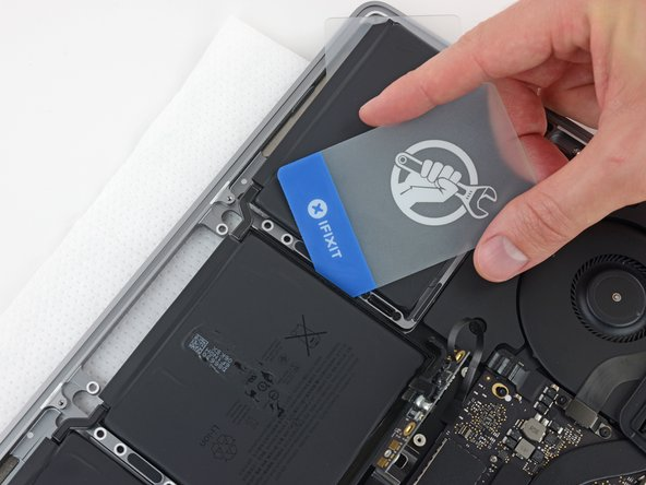 Slide a plastic card under one of the side edges of the center battery cell.