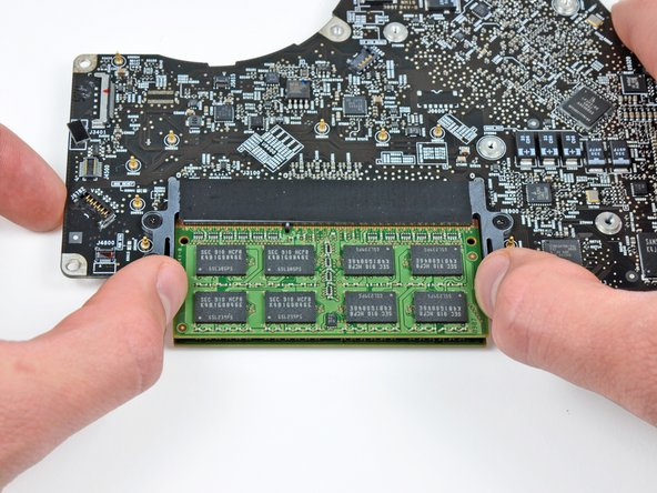 Release the tabs on each side of the RAM chip by simultaneously pushing each tab away from the RAM.