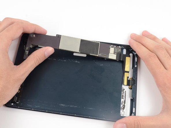 Lift the logic board and Lightning cable assembly up and pull toward the top of the iPad to remove the Lightning connector from its housing.