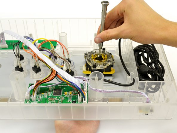 Insert a #4 Flat Head screwdriver into the shaft of the joystick and grasp the ball topper with your other hand.