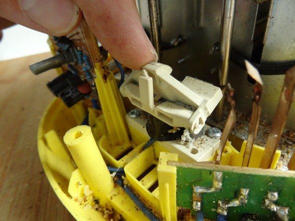 Am Magnet ist eine Kippvorrichtung aus Eisen, hier in ein Kunststoffformteil eingebettet. Wenn der Magnet anzieht, hält sie den Haken am Schieber fest.