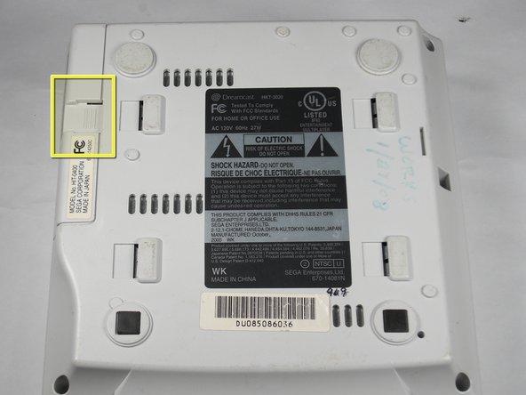 Retirez la baie d'extension en appliquant une pression sur le petit clip de la baie d'extension pendant que vous le retirez de la console.