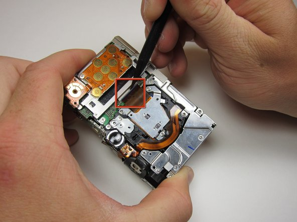 Now the photo sensor is exposed. In order to remove the ribbon cable from its port, first flip up the blue locking mechanism.