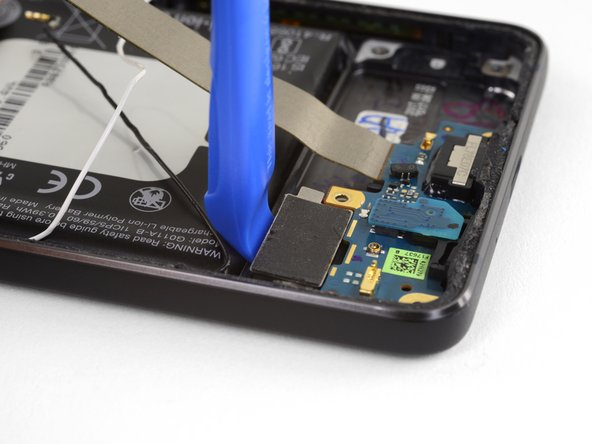 Use an opening tool the gently lift the vibration motor and separate it from the adhesive holding it to the phone.