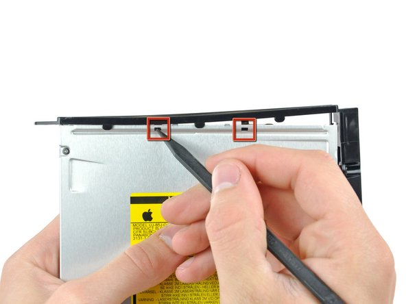 Use the tip of a spudger to press the optical drive bracket tabs out of the slots in the top of the optical drive.