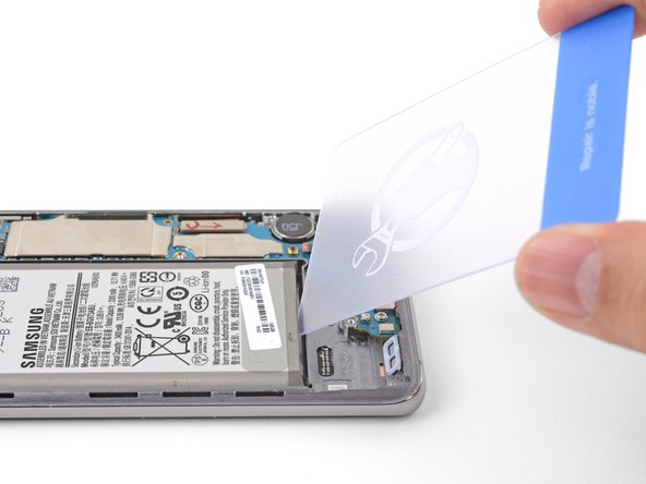 Insert the corner of an opening card into the crevice between the battery and the bottom midframe.