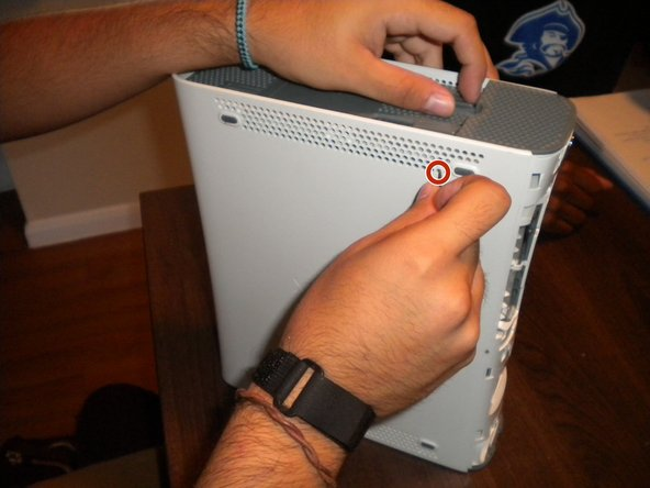 Stand the Xbox up so the bottom part is facing up. Use your nail and poke at the second hole on the second row on the side of the Xbox.