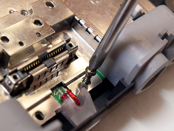 Remove the screw to the right of the LED light using the larger Phillips screwdriver.