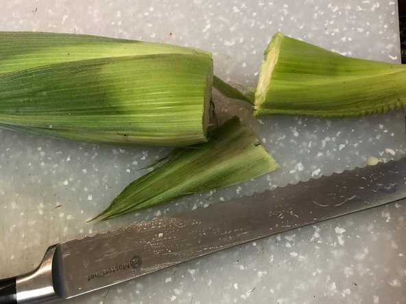 Use a very sharp or serrated edge knife and cut off the shank of the ear.  Then cut off the silts end.  FYI there is one silt for each kernel of corn.  Now peal off most of the husks but leave the corn covered with at least one layer.