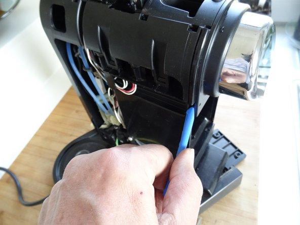 Setze ein Kunststoffwerkzeug in den Spalt unten am Kaffeeauslauf und heble ihn vorsichtig ab.