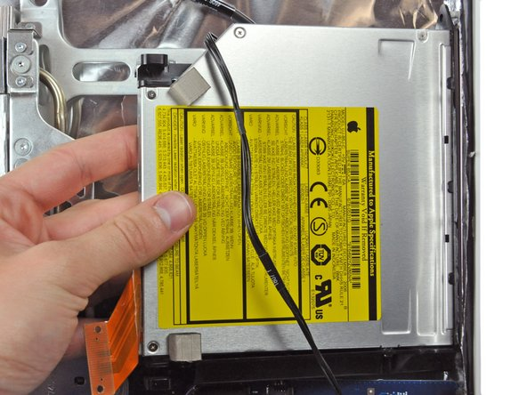 Maneuver the optical drive out of the rear case, minding the two plastic pins molded into the rear case near the open end of the optical drive that can break off.