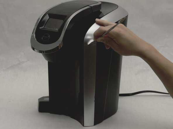 Use the metal spudger to separate the silver panel on the right side of the Keurig machine.
