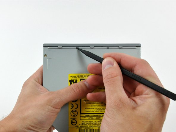 Use the tip of a spudger to push the two plastic bezel tabs away from their retaining slots on the top of the optical drive.