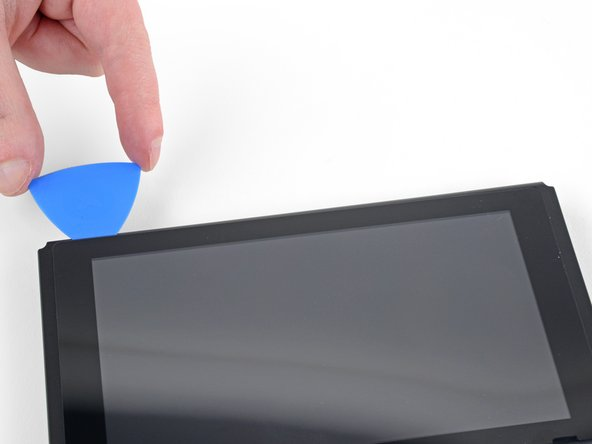 Continue sliding the opening pick along the top edge of the screen to slice the adhesive.