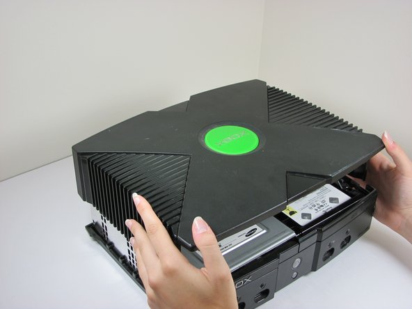 Once the bottom and top shells are no longer attached, carefully turn the Xbox right-side-up, lift and remove the top cover.