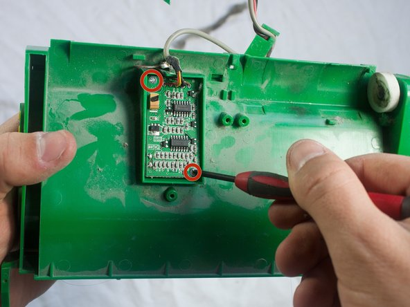 Use a Phillips #1 screwdriver to remove the two 3.5mm screws on the corners of the circuit board.