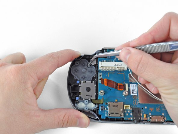 Using tweezers, gently peel the action button off the back casing assembly.