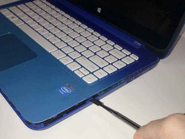 Flip the laptop back over onto its normal side up and raise the screen. Using the metal spudger, separate the keyboard surface from the bottom of the laptop.