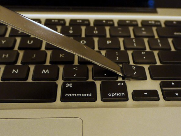 Use a spudger or plastic opening tool to pry up sticky keys.