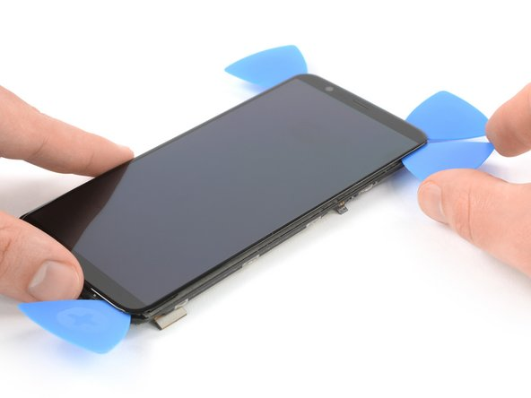 Insert a fifth opening pick and slide it along the right edge of the phone to cut the remaining adhesive.