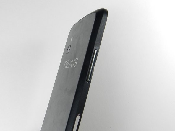 To remove the volume button, push the button in towards the center of the phone using a spudger.