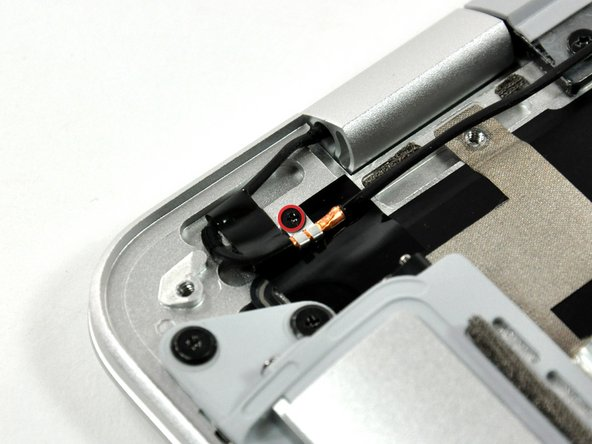 Remove the single Phillips screw securing the microphone cable ground loop to the upper case.