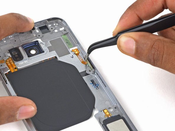 Using the angled tweezers, grip the power button bracket and pull it out of its socket.