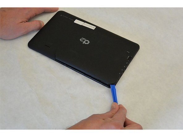 Wedge the opening tool in the space between the back and the front of the tablet.