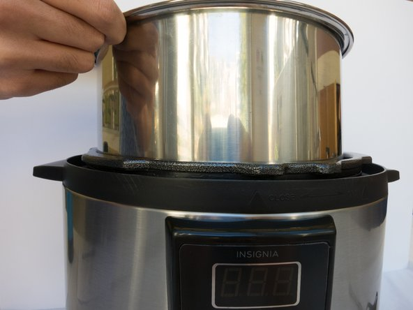 Lift the silver inner pot out of the pressure cooker base.