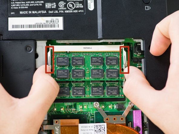 Push out on the first set of metal tabs to release and remove the top RAM chip.