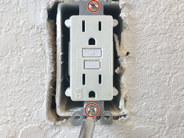 Using #2 flat-head screwdriver, unscrew the top and bottom screws holding the outlet onto the wall.