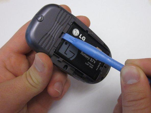 Insérez un outil d'ouverture en plastique dans le point de libération de la batterie situé au-dessus de la batterie.