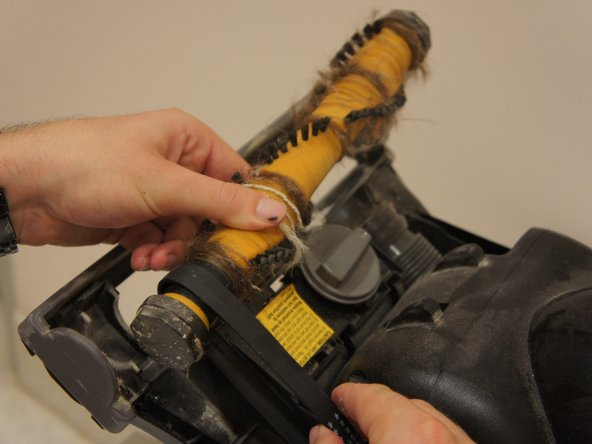 Once the brush roll is displaced from the base, detach the belt from the brush roll in order to clean the brush roll.