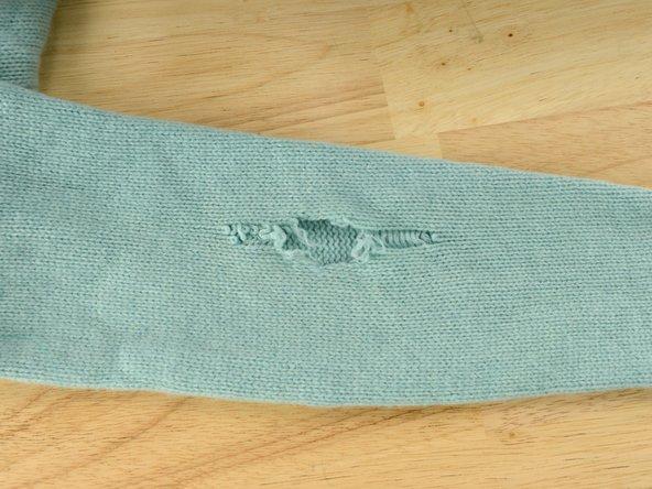Stendere la maglia su una superficie piana, con lo strappo rivolto verso l'alto.