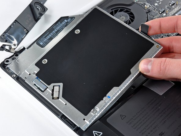Lift the optical drive near its connector and pull it away from the upper case to remove it from the computer.
