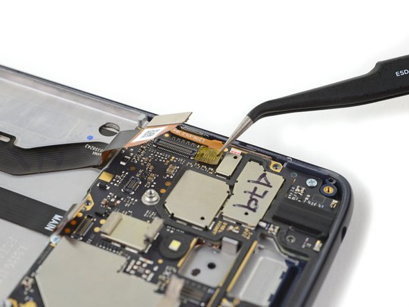 Use a pair of tweezers to remove the piece of tape covering the side button flex cable connector.