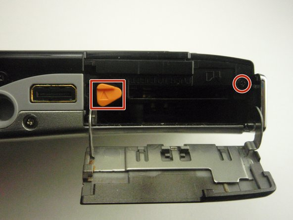 Open the battery door by sliding it in the direction of the arrow to reveal a hidden screw on the opposite side of orange lever.