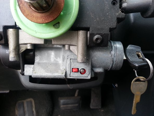 "Sit in the car facing the steering wheel. Lean to the left  to locate the two ""torx head"" screws on the ignition. Remove these."