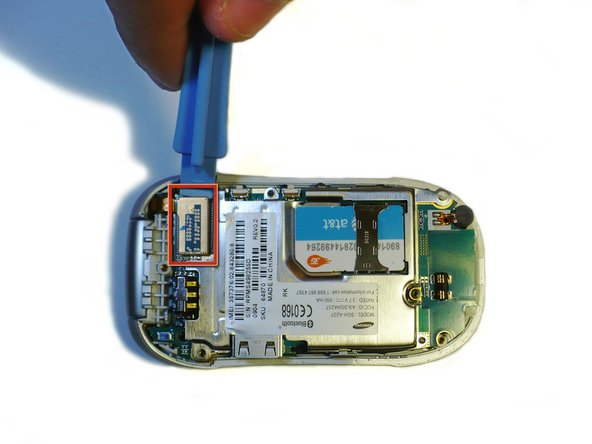 Detach the tab from the logic board by using iPod Opening Tool (as shown).