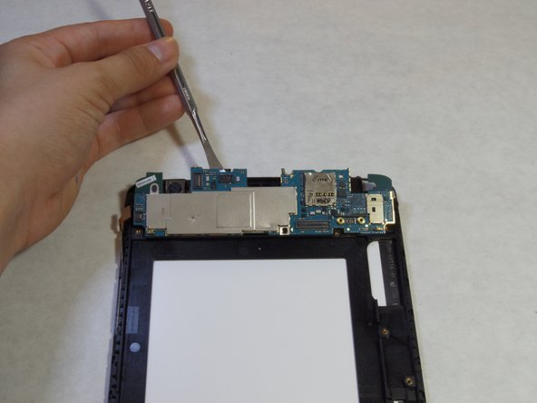 Use a plastic opening tool to lift the motherboard out of the device.