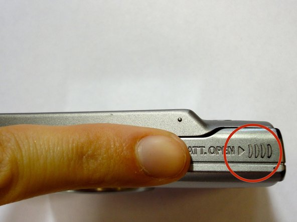 Using your finger, apply pressure to the grooves at the top right corner of the camera that is highlighted in red. Slide the door to the battery compartment open.