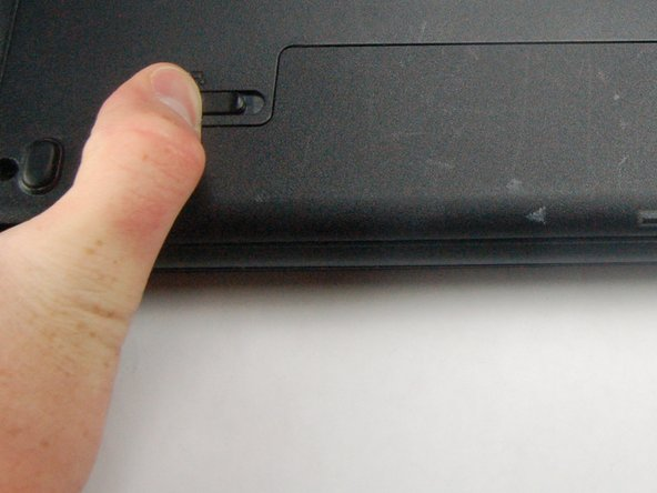 Flip computer over to the bottom and slide the latches on both sides of battery outwards.